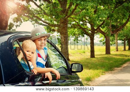 Children looking out of window from a car. Boys are going to vacation on summer day