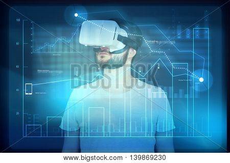 Young bearded man in virtual reality glasses is using digital monitor with diagram and analyzing virtual data