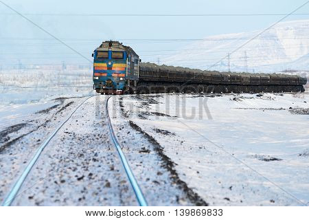 Freight train moving on snow-covered tracks. Arctic tundra.