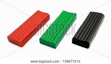 3 Pieces Of Plasticine Red, Green And Black Isolated On White