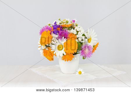 Bouquet of chamomile, marigold and cornflowers in a white vase on a light background.