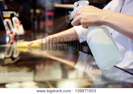Maid service cleaning glass table with chemicals spray and rag