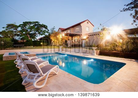House And Swimming Pool Decoration At Evening With Flashing Ligh