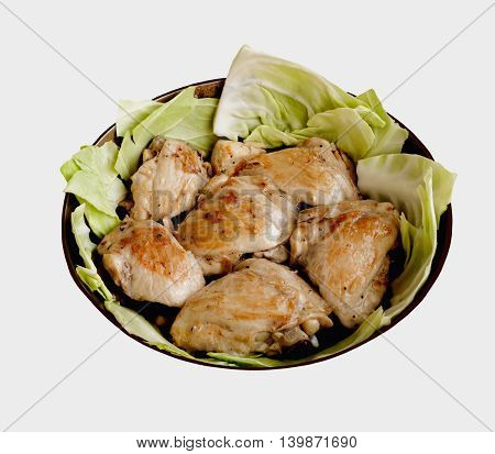 Slices of fried chicken with cabbage in a frying pan