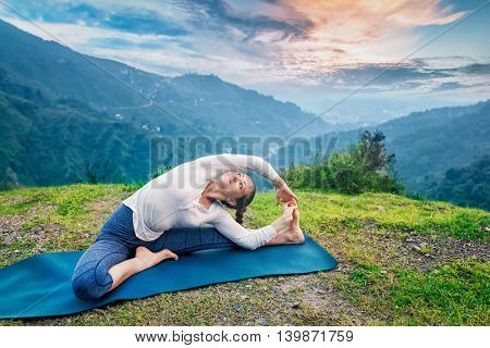 Yoga outdoors - young sporty fit woman doing Hatha Yoga asana parivritta janu sirsasana - Revolved Head-to-Knee Pose - in