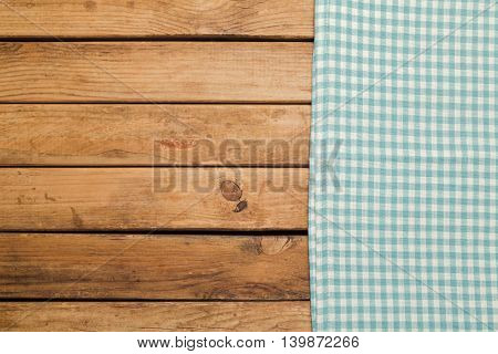 Wooden deck background with checked blue tablecloth