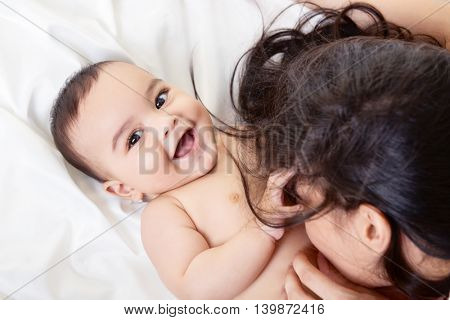 Young mother playing with her baby on white silk bed sheet. Cute mixed race bab boy has fun with mum, high key.