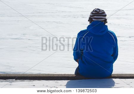 man back listening music on concrete wall by the lake during winter snow on a sunny day