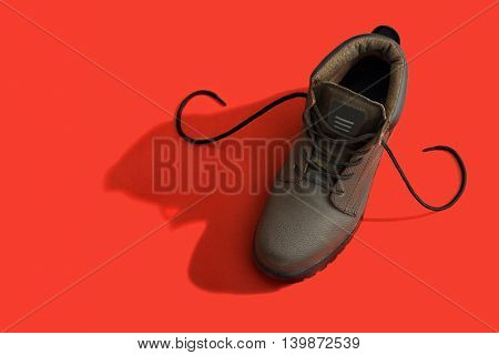 Brown safety boots over a red background