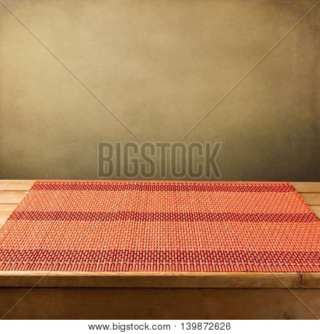 Bamboo tablecloth on wooden table over grunge background. Ready for product display monage