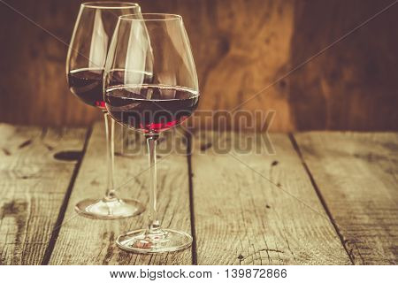 Glasses with red wine on rustic wood background, copy space, toned