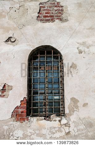 A semicircular window with bars in an old brick building
