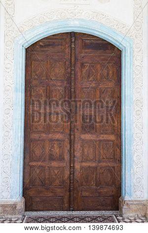 ancient wooden carved door closed in white stone building
