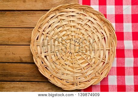Wicker plate on checked tablecloth over wooden background