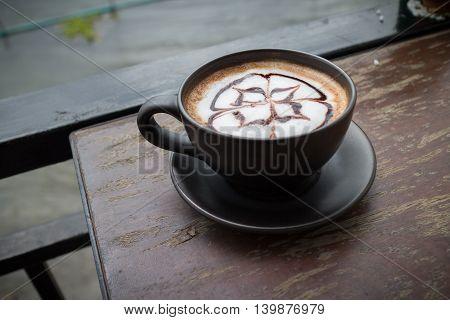Hot coffee with foam milk art in afternoon break. Coffee mocha on the wood desk.(selective focus vintage effect)