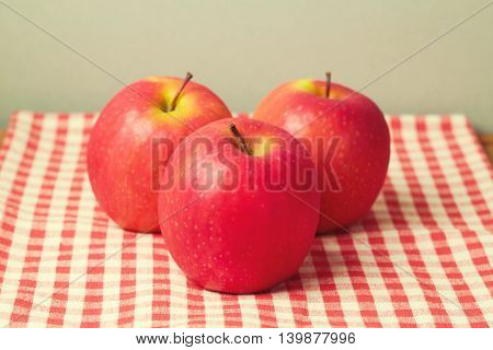 Three fresh apples on red checked tablecloth