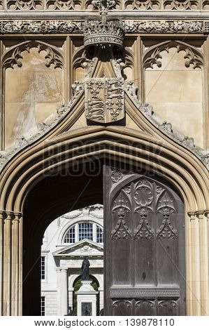A close-up of the Royal Crown and Coat of Arms on the gatehouse of King's College in Cambridge UK.
