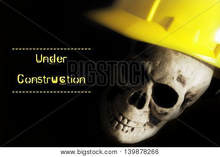 An under construction alert with the skull of a labourer who worked himself to the bone.