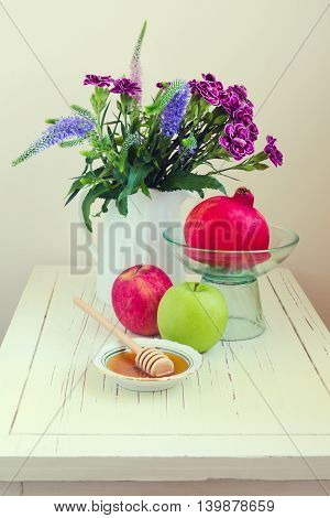 Apple with honey pomegranate and flowers on wooden white table