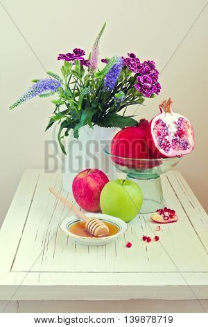 Still life with apple honey pomegranate and flowers on wooden white table
