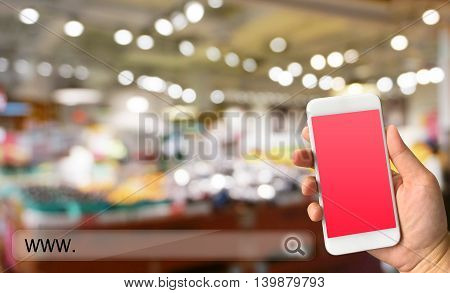 Woman hand holding smartphone against blur bokeh of store background online shopping concept