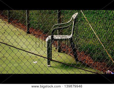 Green plastic chair in a tennis court