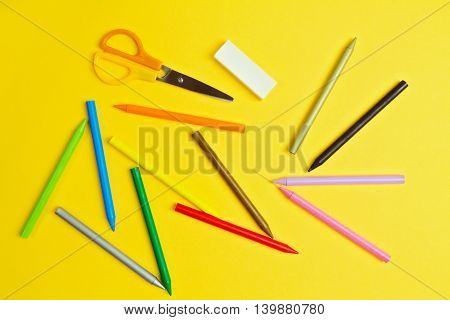 Color pencils and scissors on yelloow paper background