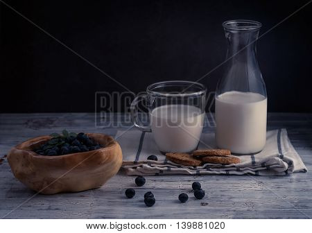 Still life with cookies, milk and blueberry on dark background in rustic style