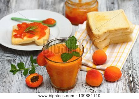 Fresh apricot smoothie in glass apricot jam on toast and around apricots around