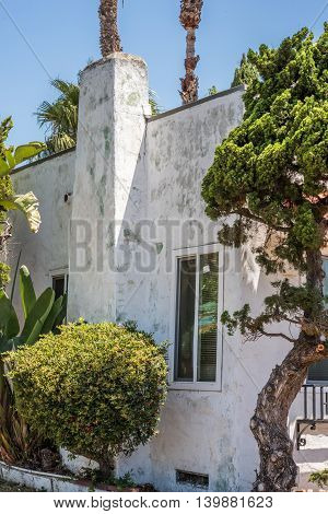 aged peeled white cottage wall with window and chimney shrubs and cypress tree