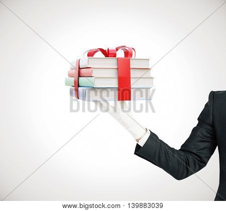 Businessman hand holding stack of colorful books tied up with a ribbon on grey background. 3D Rendering