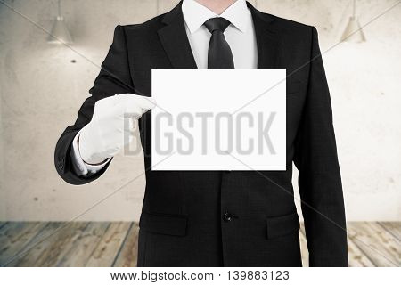 Business man holding blank card on concrete interior background. Mock up