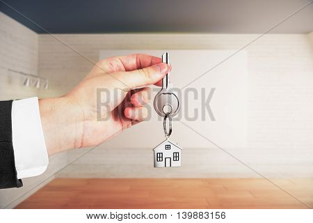 Businessman holding keys on interior background. Real estate and mortgage concept