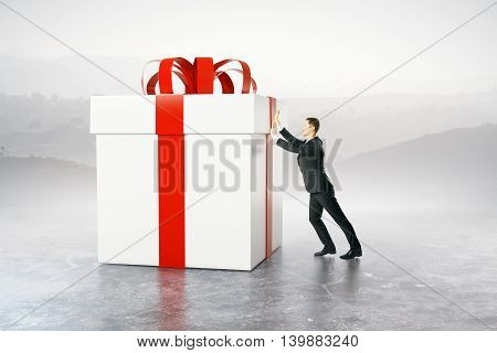 Businessman pushing huge present box on abstract background. 3D Rendering