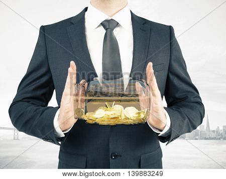Businessman in suit holding glass jar with golden coins on abstract foggy city background. Savings concept