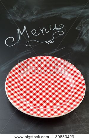 Empty checked plate on chalkboard with word menu