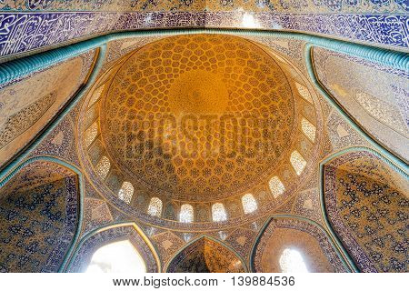 ISFAHAN. IRAN - OCT 14, 2014: Dome inside the ancient persian mosque with traditional tiled ceiling and arches on October 14, 2014. The 3rd largest city of Iran Isfahan is example of Iranian Islamic culture