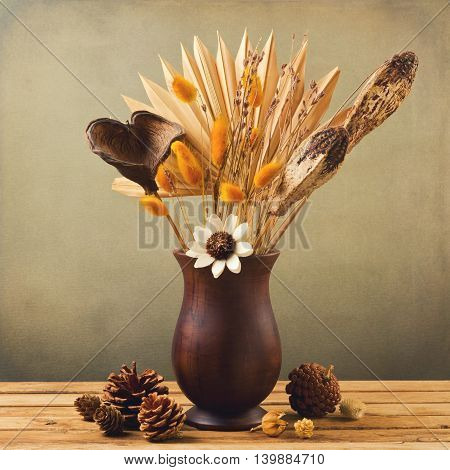 Dried flowers in wooden vase with pinecorn over grunge background