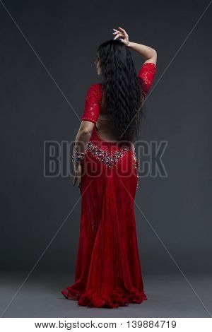 Young beautiful exotic eastern women performs belly dance in ethnic red dress on gray background. Studio shot