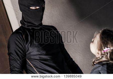 Child Abuse Concept. Trafficking of Children Conceptual Photo. Caucasian Girl and the Men in Black Mask.