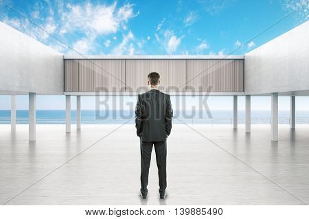 Businessman looking at concrete exterior by the sea on bright blue sky background. 3D Rendering