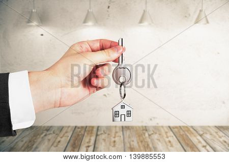 Businessman holding keys on empty interior background. Real estate and mortgage concept