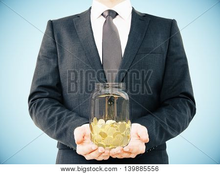 Businessman in suit holding glass jar with golden coins on light blue background. Savings concept