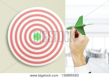 Targeting concept with businessman hand playing darts on blurry office background. 3D Rendering