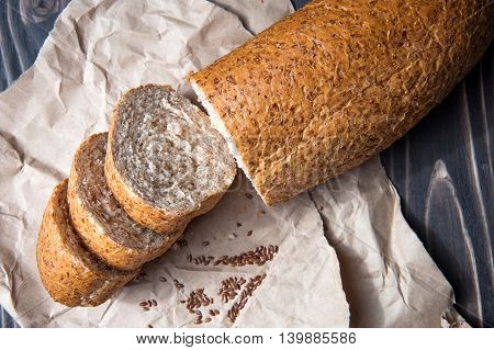 Bread with bran and seeds. Sliced is on the board for cutting