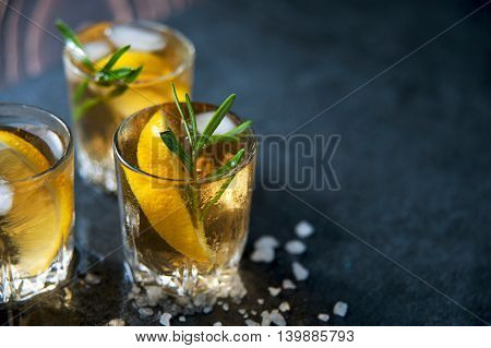 Alcohol cocktail with ice and smoking rosemary on dark table with lemon and salt