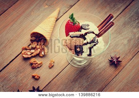 Ice cream sundae, waffle cone, walnuts and strawberry