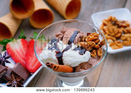 Ice cream sundae, chocolate, walnuts and sliced strawberry