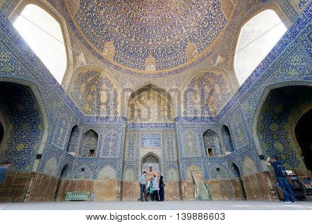 ISFAHAN, IRAN - OCT 14, 2014: Tourists watching great artworks with tiles of historical persian mosque on October 14, 2014. The 3rd largest city of Iran Isfahan is outstanding example of Islamic culture