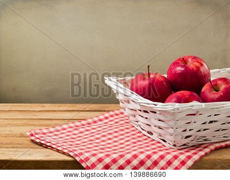 Apple in basket on wooden table with checked tablecloth